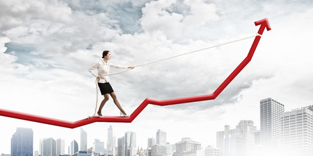 Image of businesswoman standing on graph  Income and profit Foto de archivo