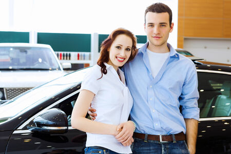 Two pretty young people smiling standing near car photo