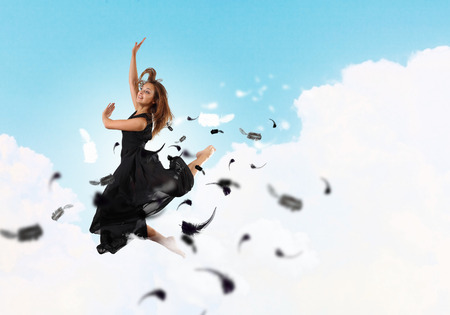 Young girl flying among the feathers like a bird photo