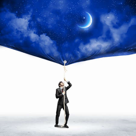 commercialism: Image of businessman pulling banner with illustration  Day and night concept