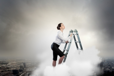 Image of young ambitious businesswoman climbing ladder  Promotion concept photo
