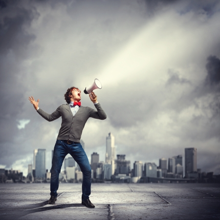 Portrait of young man shouting loudly using megaphone Stock Photo