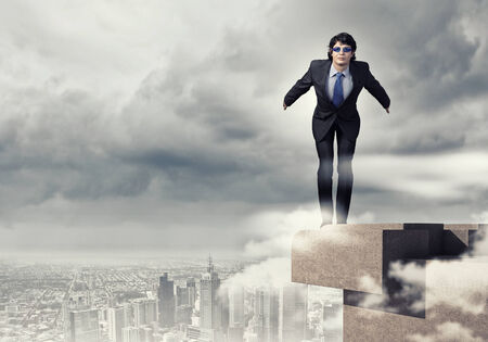 dangerous ideas: Image of young businessman in goggles jumping from top of building Stock Photo