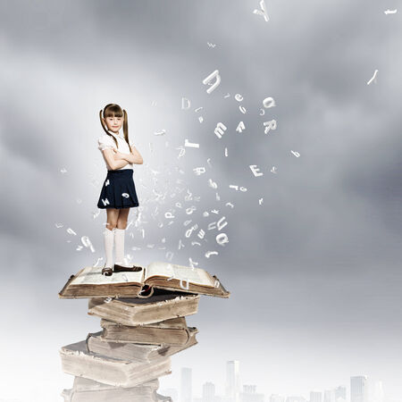 able to learn: Image of cute school girl standing on pile of books Stock Photo
