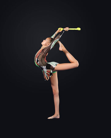 Young cute woman in gymnast suit show athletic skill on black  photo