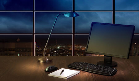 sight seeing: Work place in the office at night with a city view from window Stock Photo