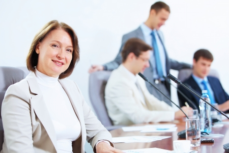 Image of businesswoman at business meeting with three businessmen in background photo