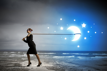 commercialism: Image of businesswoman pulling moon with rope
