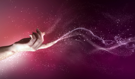 conceptual image: magical hand conceptual image with sparkles on colour background