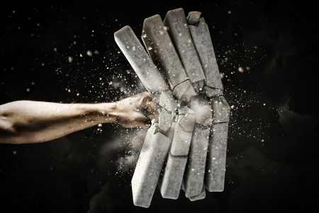 Close up of human hand breaking bricks Imagens