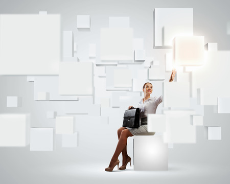 multitouch: Image of elegant businesswoman sitting on white cube touching media button