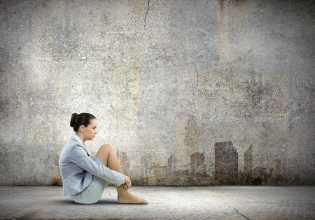 incapacity: Image of young upset businesswoman sitting alone