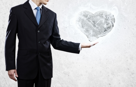 hard love: Businessman holding stone in shape of heart in palm