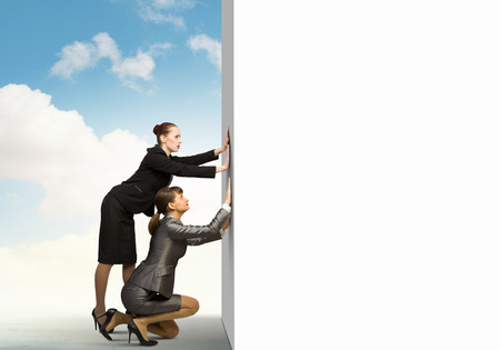 Image of two businesswomen pushing blank wall  Place for text photo