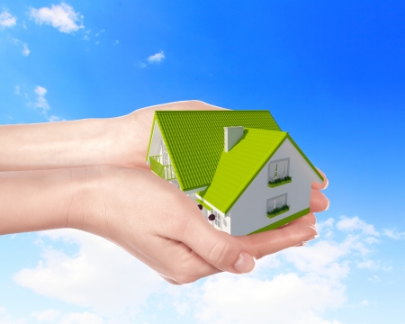 The house with colour roof in human hands Stock Photo - 24425413