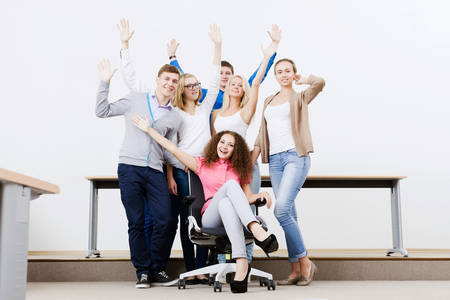 woman screaming: Young happy people in classroom screaming joyfully Stock Photo