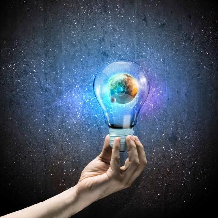 人間の手と地球惑星内部の電球を保持しているイメージ
