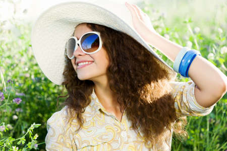 Young beautiful girl in hat and glasses sitting in grass photo