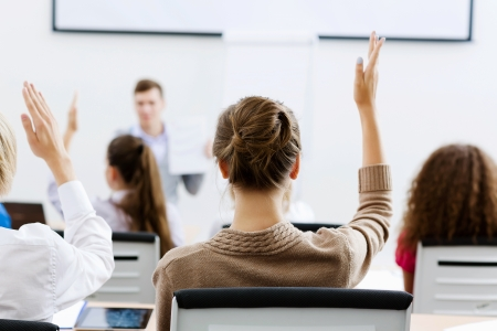 training: Young teacher in classroom standing in front of class Stock Photo