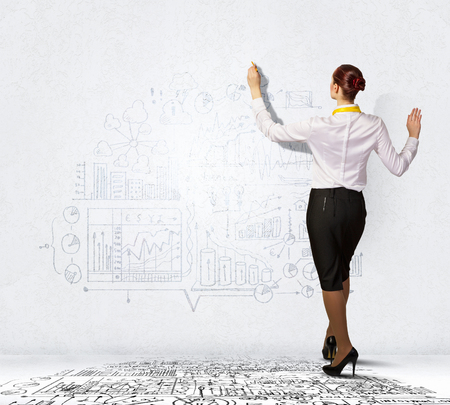 Businesswoman standing with back drawing business ideas on wall photo