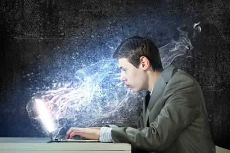Young man in suit looking astonished in laptop  Surfing the internet photo