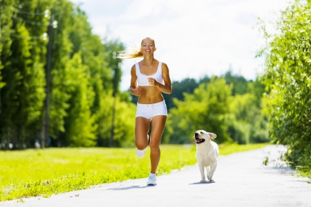run woman: Young attractive sport girl running with dog in park