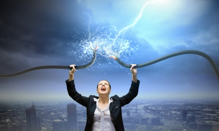 volts: Image of businesswoman holding electrical cable above head Stock Photo