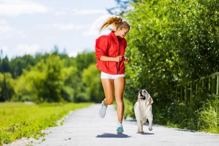 perros jugando: Joven atractiva chica de deporte corriendo con el perro en el parque