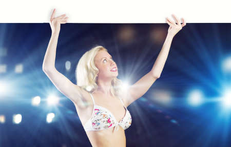 Girl in swim wear holding white blank banner above head  Place for text photo