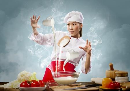 Cocina asiática femenina con la magia contra el color de fondo Foto de archivo - 24603634
