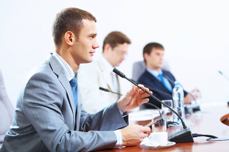 Image of three businesspeople at table at conference photo
