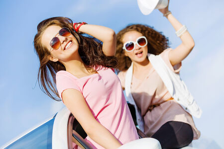 Young pretty women leaning out of car window photo
