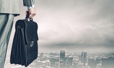 街を見てのスーツケースを持ったビジネスマンの背面図