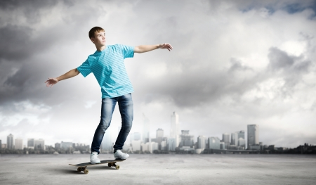 Skater in jeans riding on road against city background photo