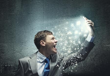 empresario enojado: Hombre de negocios enojado gritando en el tel�fono m�vil con furia Foto de archivo