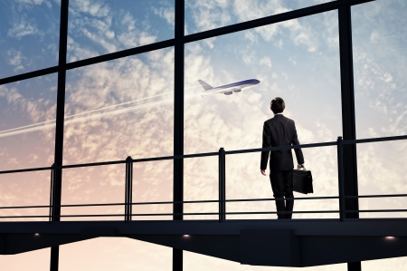 Image of businessman at airport looking at airplane taking off photo