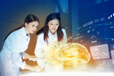 Image of two women doctors examining virtual image of brain photo