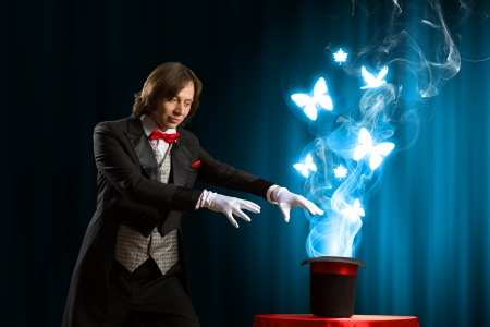 Image of magician showing tricks with magic hat photo