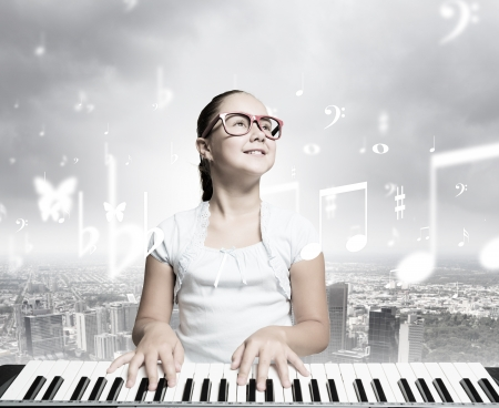 Young girl sitiing at digital piano with red glasses photo