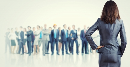 group  accountant: Powerful businesswoman standing with back with business team at background