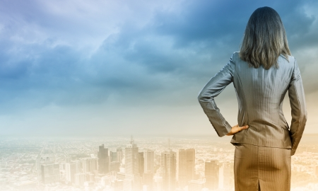 power: Back view of confident businesswoman with arm on waist