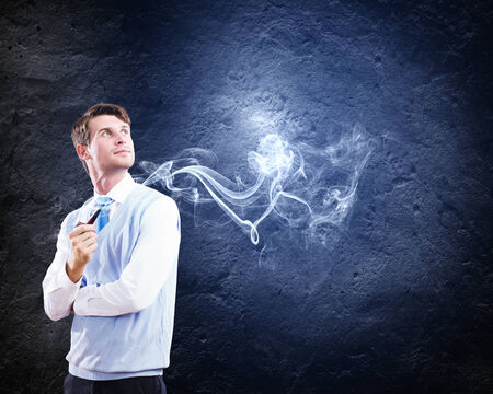 Young handsome businessman in fumes smoking pipe Stock Photo