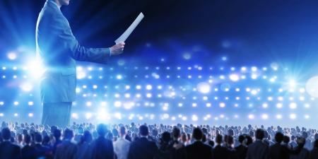 public speaker: Back view of businessman speaker standing on podium in lights