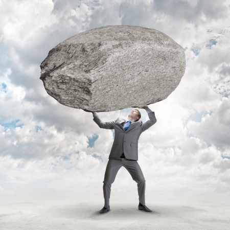 burdensome: Powerful businessman holding huge stone above head Stock Photo