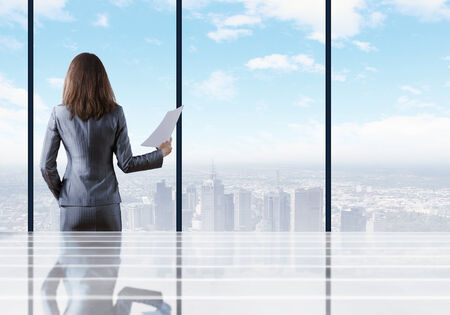 businesswoman standing: Businesswoman standing with back against office window holding documents in hand