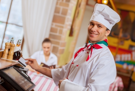 white card: Image of handsome chef inserting card in terminal Stock Photo