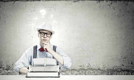 Young funny man in glasses writing on typewriter Stock Photo