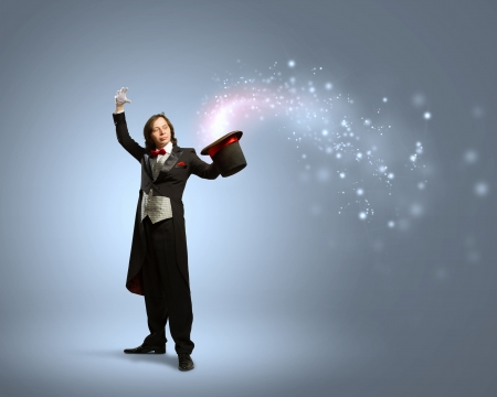 Image of magician holding hat with lights and fumes going out photo