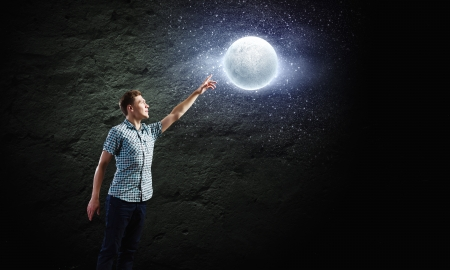 Young man and moon planet against dark background photo