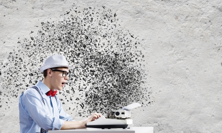 Young funny man in glasses writing on typewriter photo